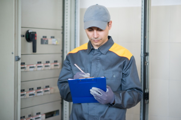 Electrician writing a document while inspecting a panel